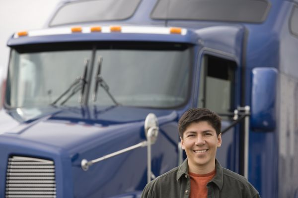 truck driver standing in front of blue semitruck